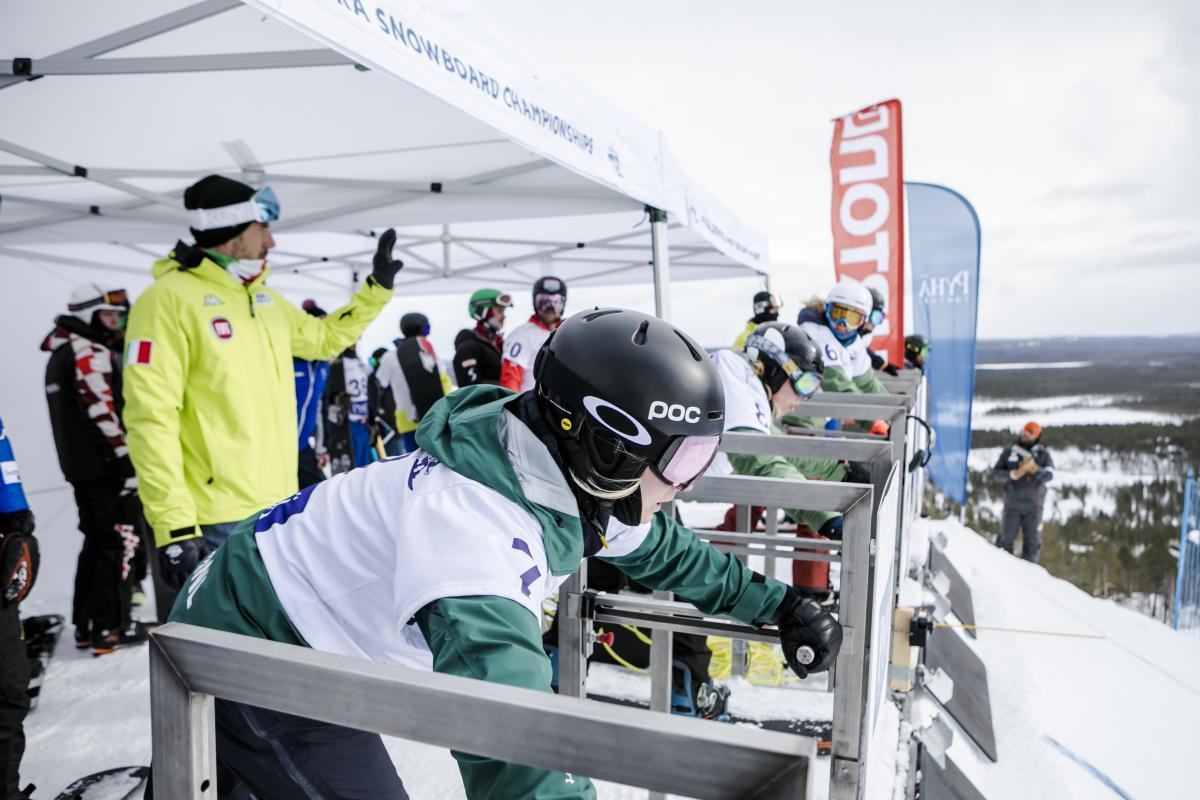 Female snowboarders line up at the start gate ready to go