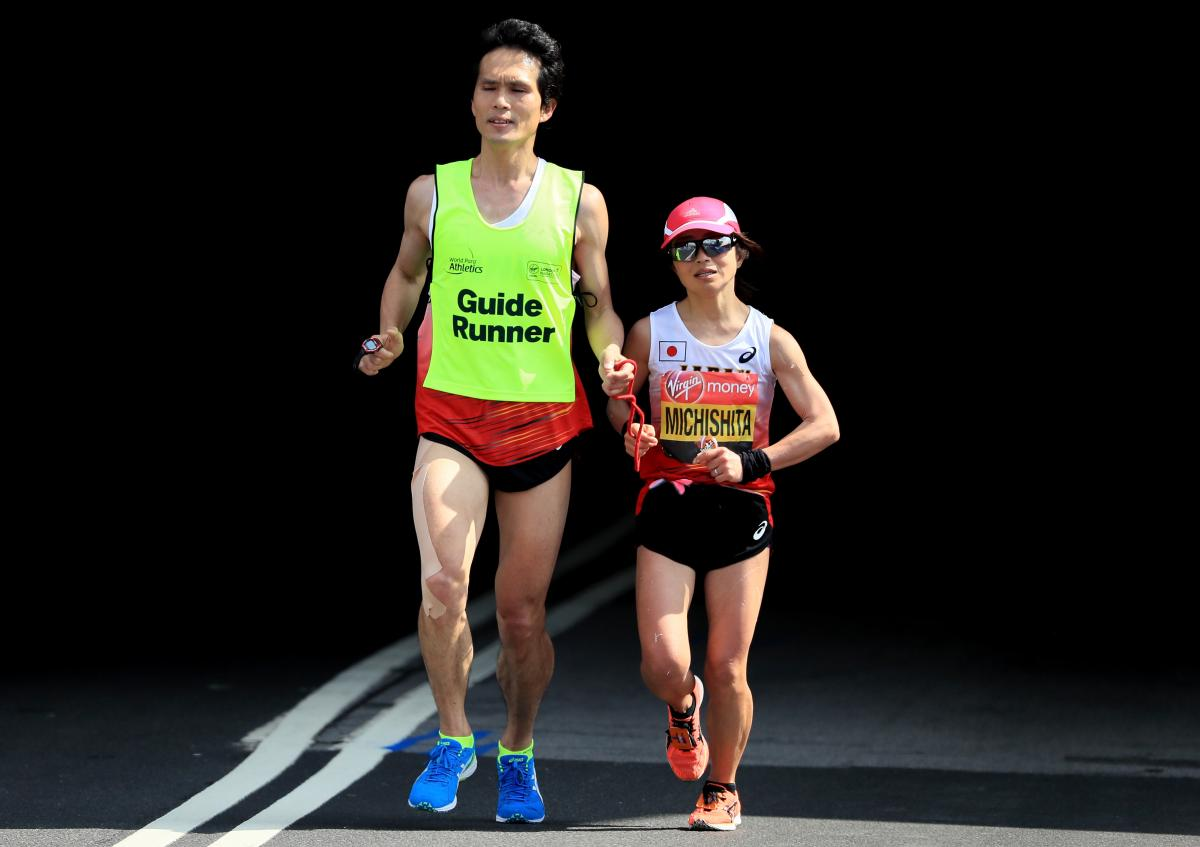 female vision impaired runner Misato Michishita running on the street with a male guide