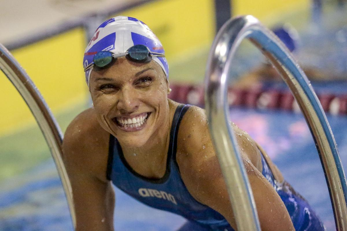 Female Para swimmer Maria Carolina Gomes smiles in the pool while leaning on the steps