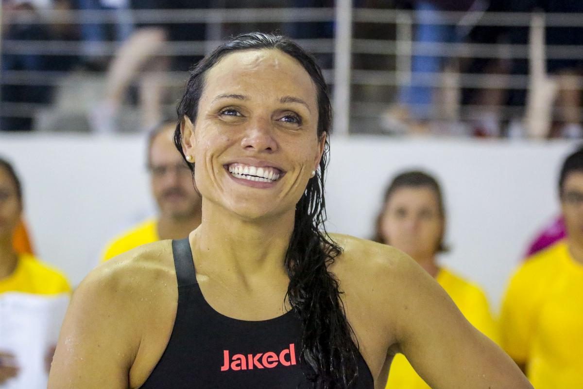 Maria Carolina Gomes smiling while wearing her swimsuit