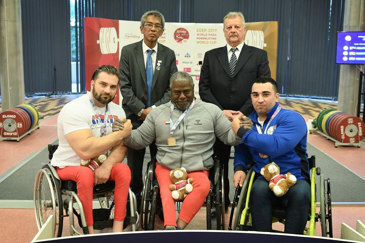male Para powerlifter Mohammed Khamis Khalaf in the middle of two other powerlifters on the podium with their arms around eachother