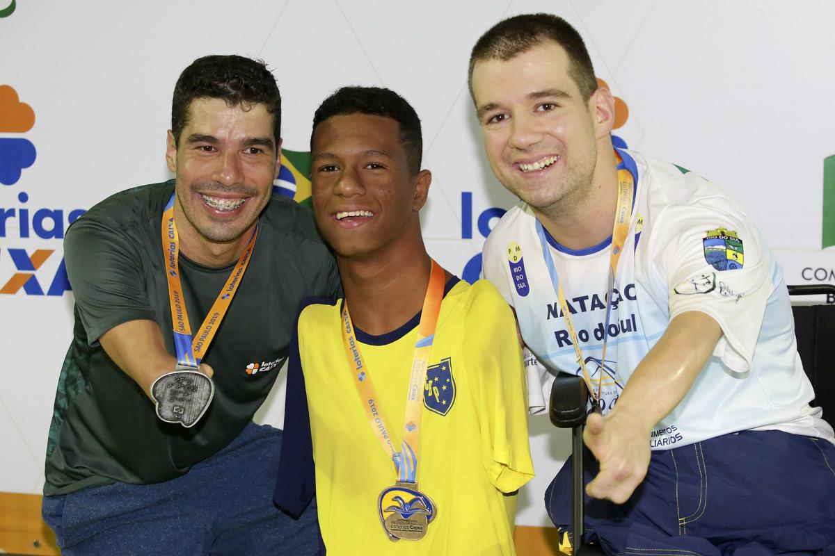 three male Para swimmers with their medals on the podium