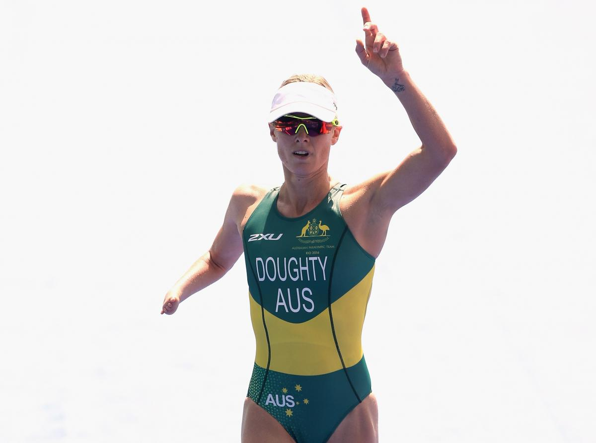 female Para triathlete Kate Doughty raises her hand and points to the sky as she crosses the finish line