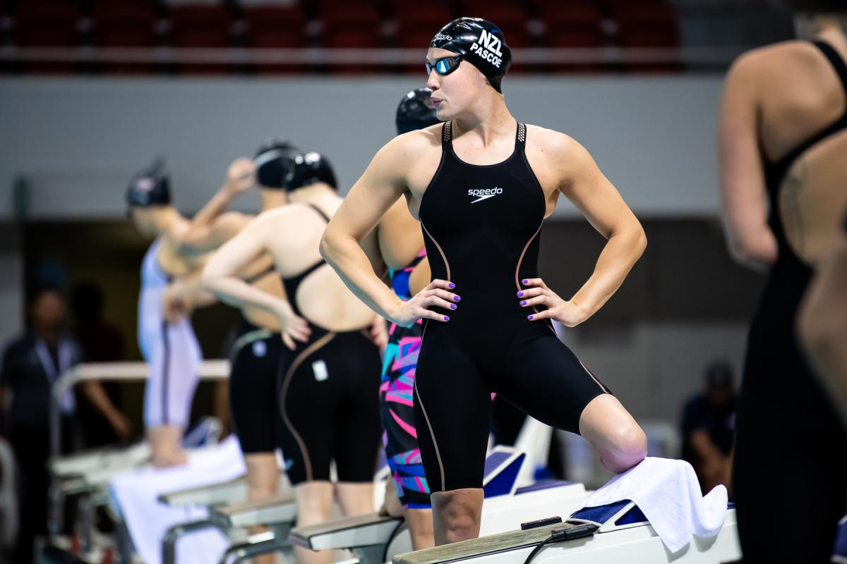 New Zealand female swimmer puts hands on hips and prepares to take her mark in pool