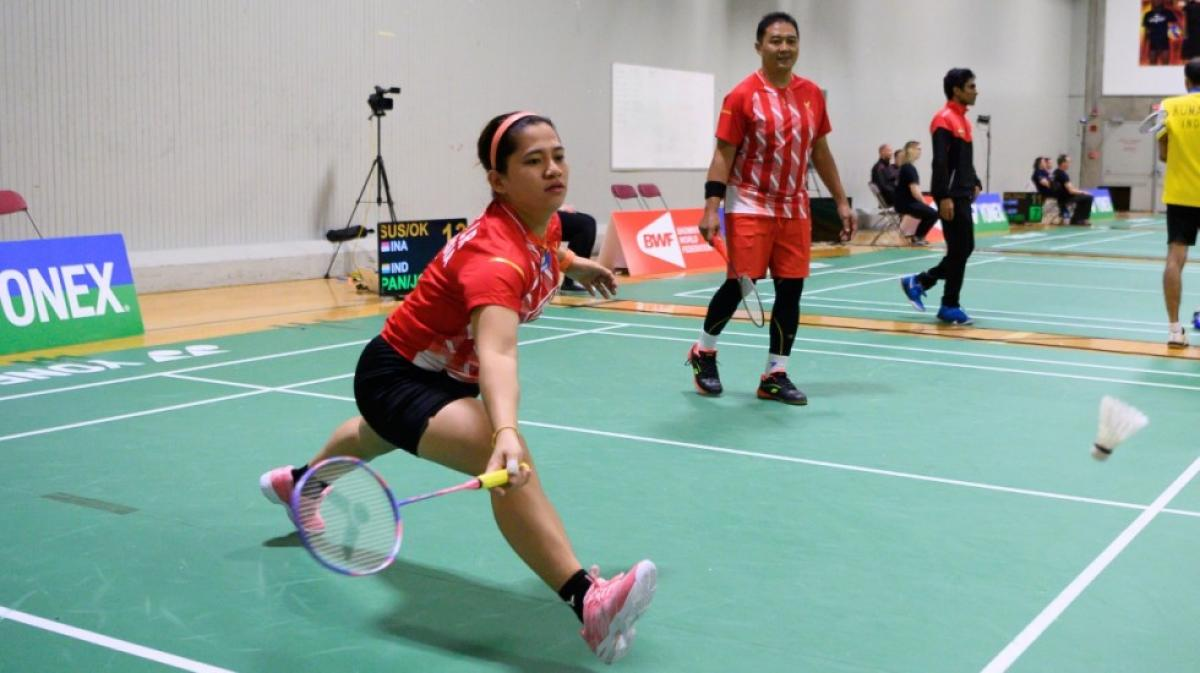 Indonesian female badminton player lunges for the birdie
