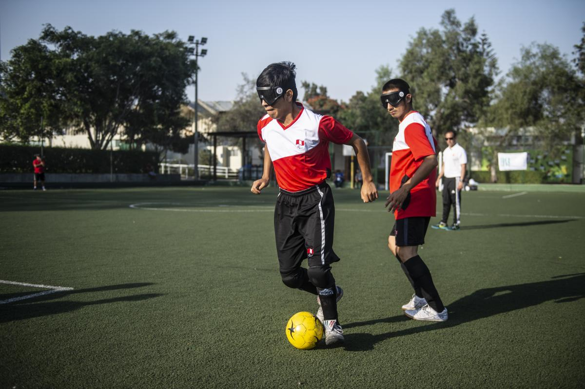 Blind football player wearing Peruvian shirt in posession of the ball