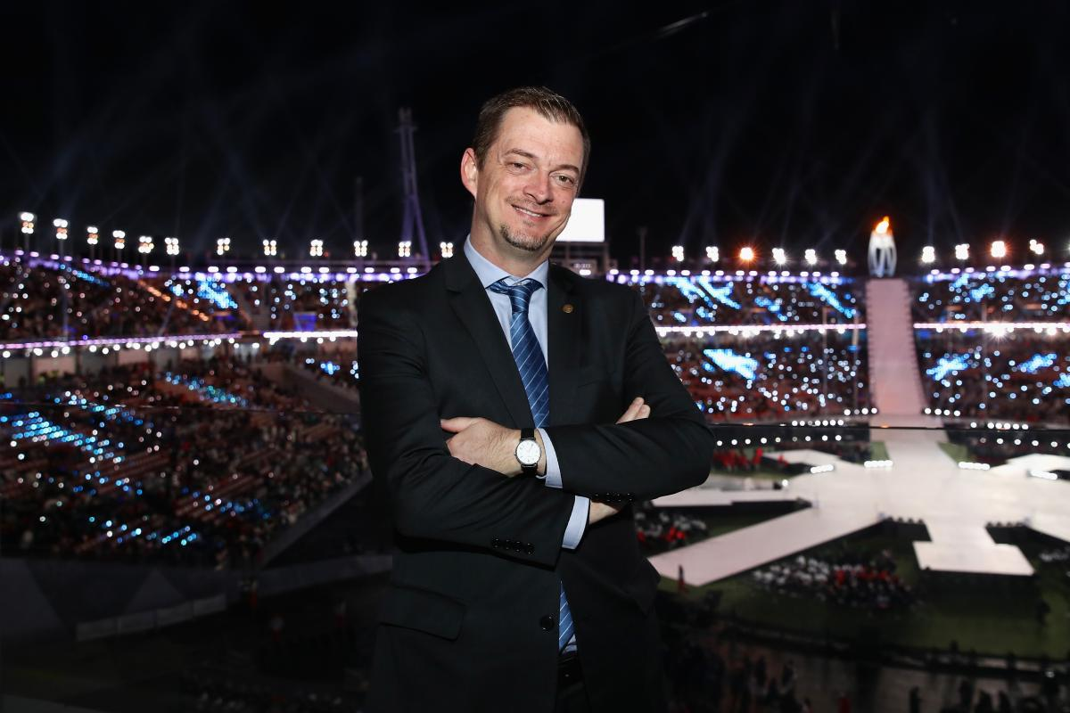 IPC President Andrew Parsons smiles and crosses arms with the PyeongChang 2018 stadium in the background during the Closing Ceremony