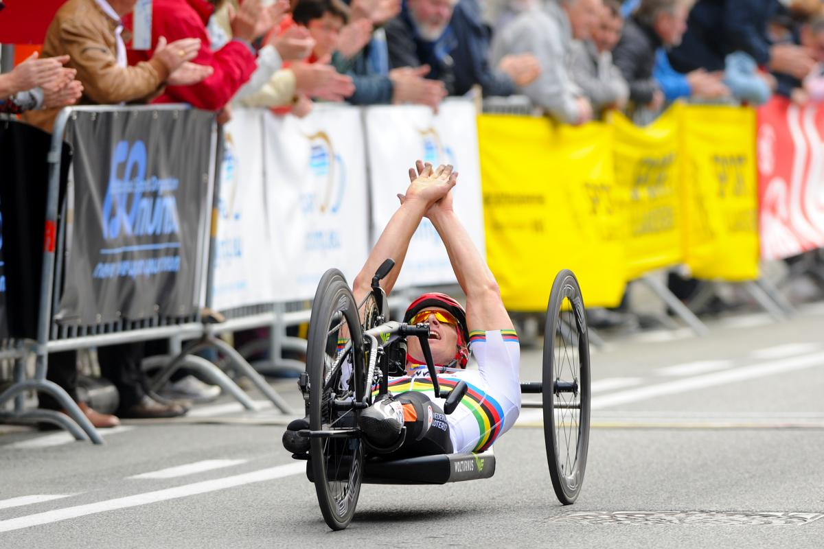 Dutch Para cyclist Jetze Plat celebrates with his hands up while crossing the finish line