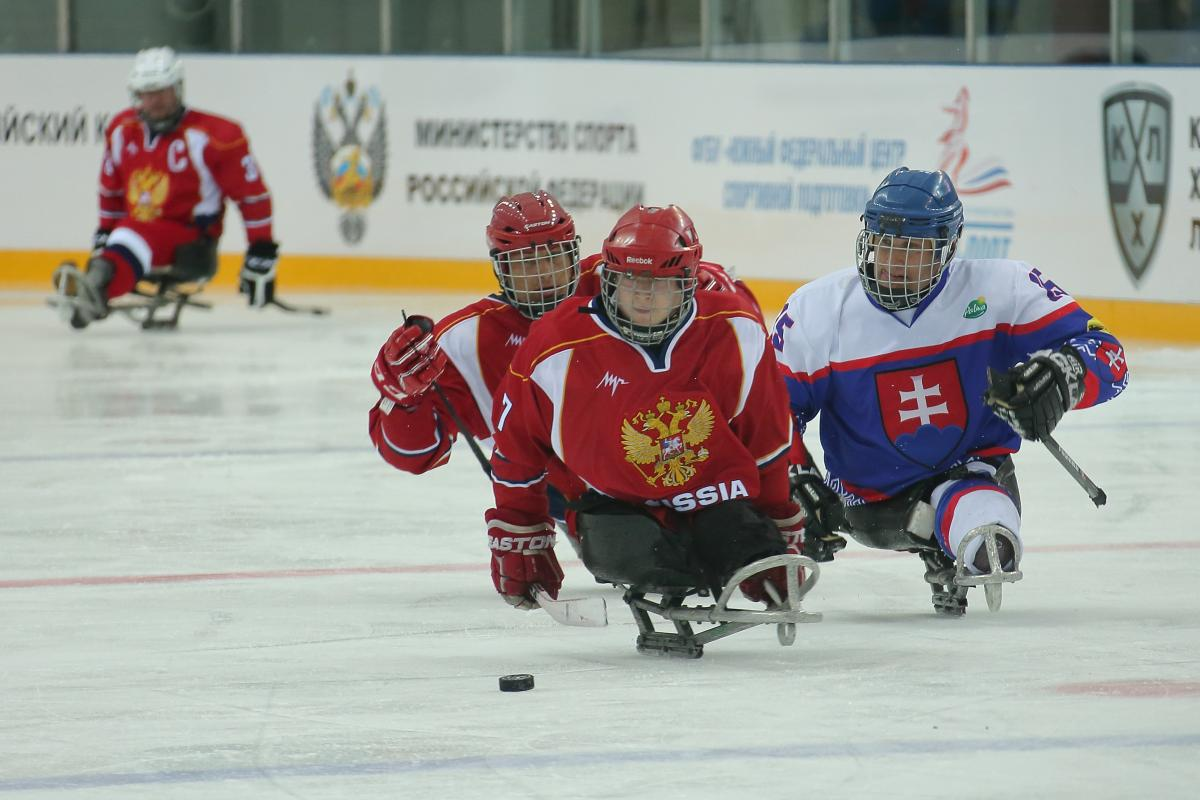 Two Russia Para ice hockey players and one Slovakian race for the puck