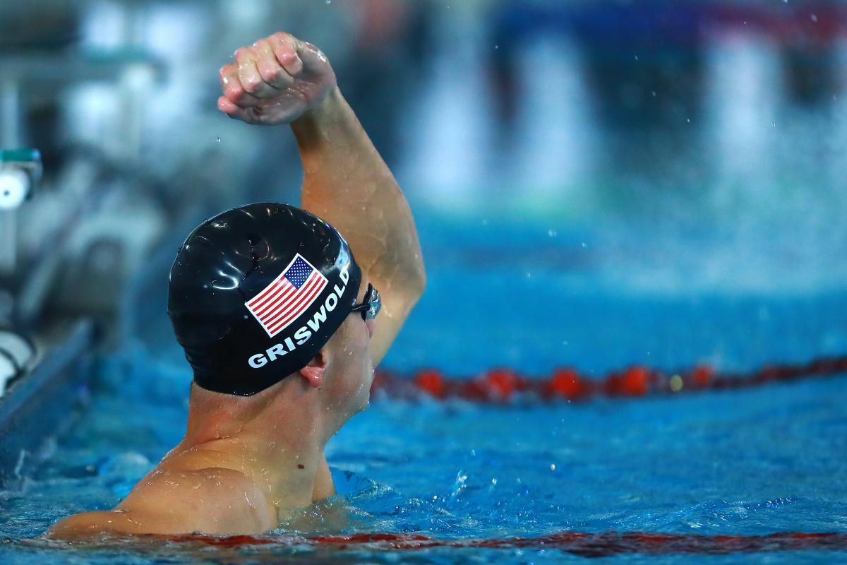 male Para swimmer Robert Griswold punches the air in the pool after winning a race