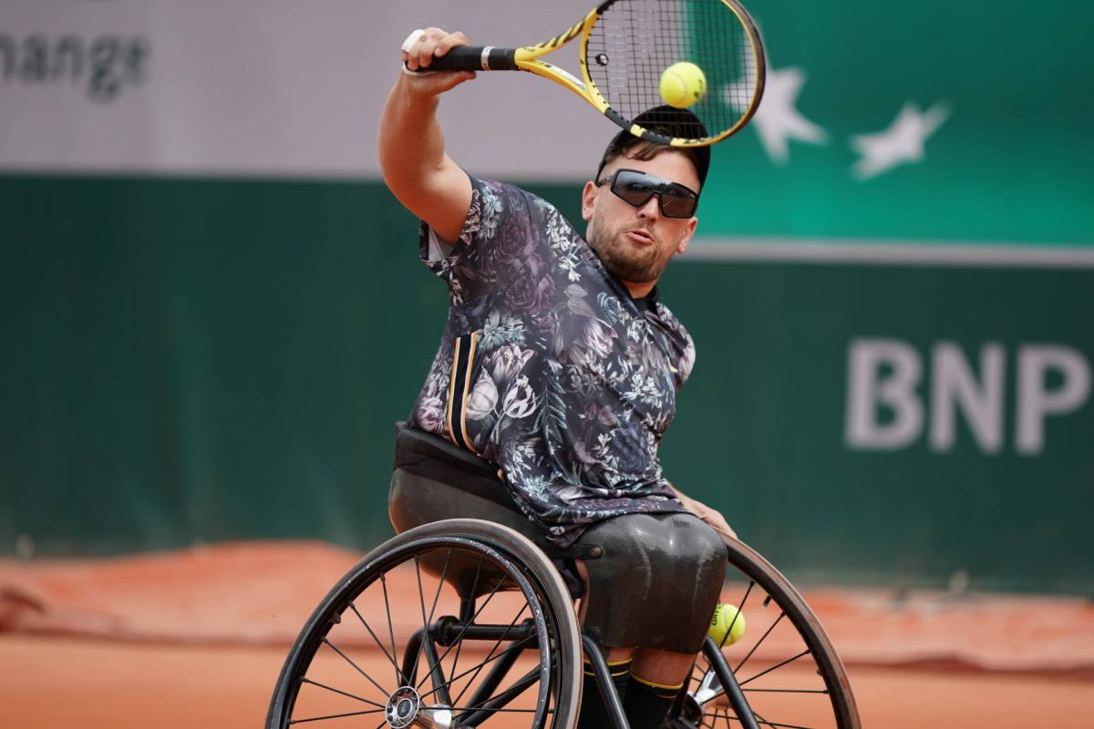 male wheelchair tennis player Dylan Alcott hits a backhand on a clay court