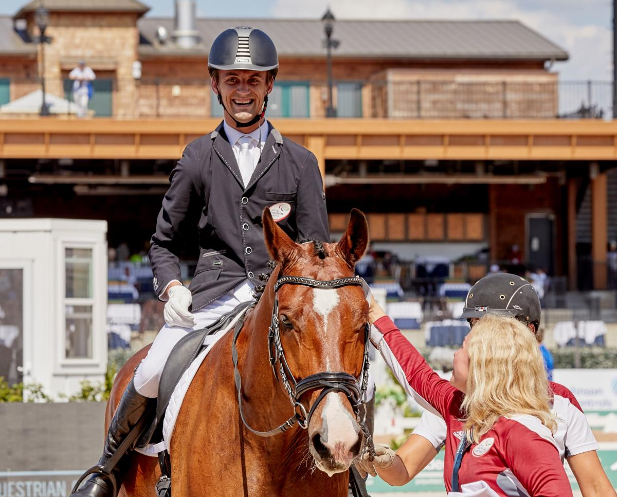 Latvian male dressage rider with celebral palsy smiles on a horse