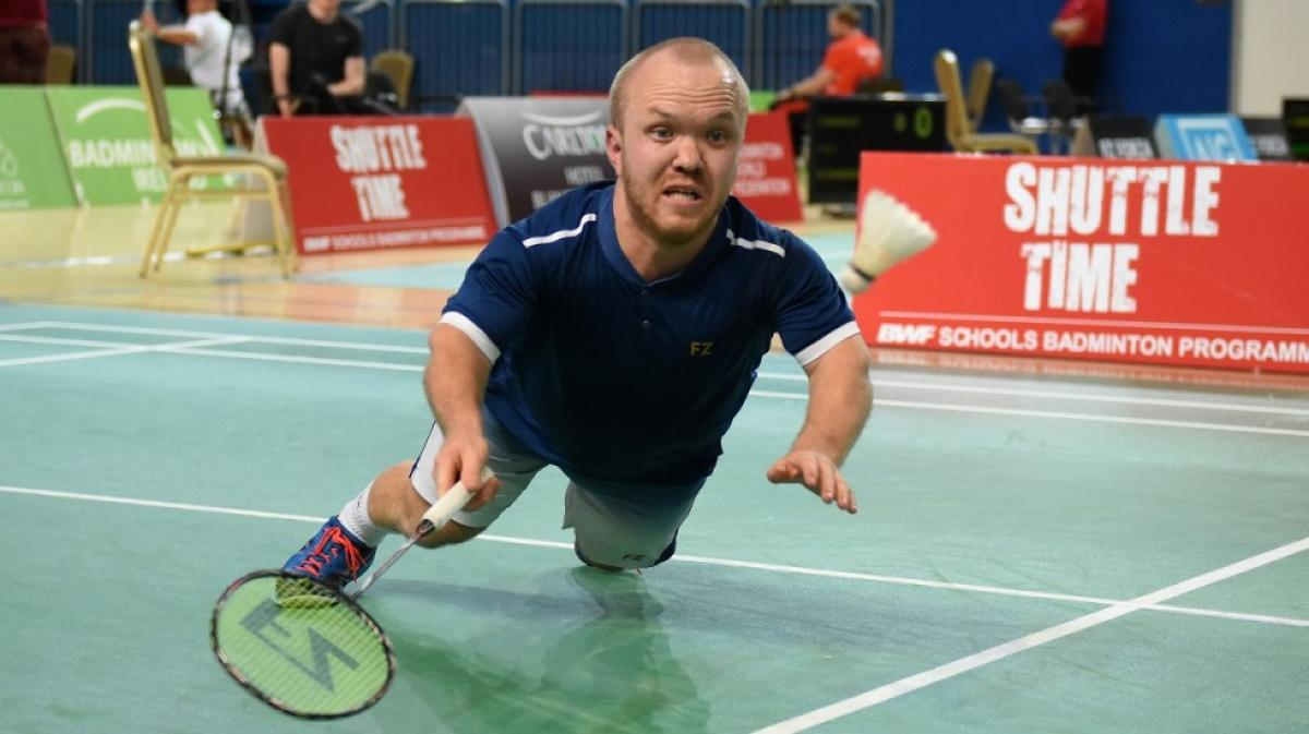 Short statured English badminton player dives for the birdie