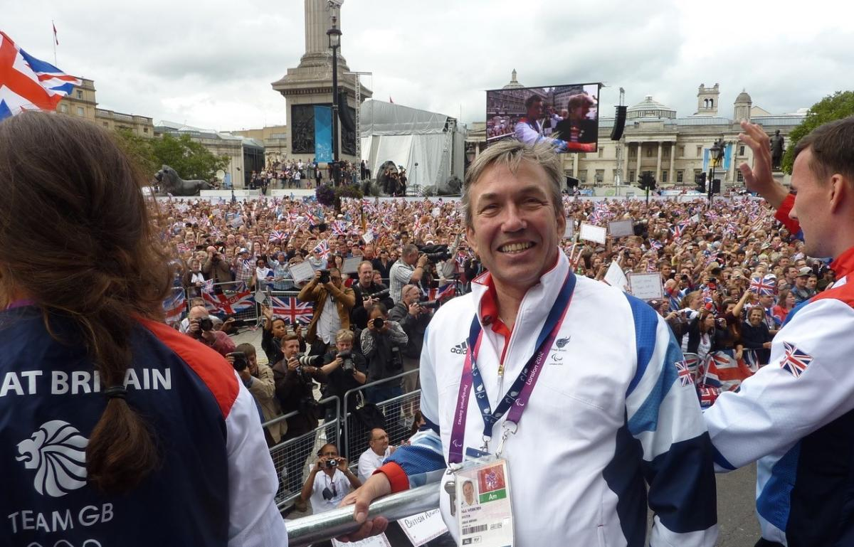 British man in wheelchair smiling in front of a big crowd of people