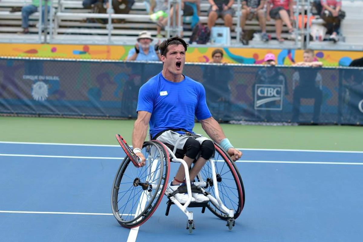 Argentinian wheelchair tennis player Gustavo Fernandez screams with joy on the court after winning gold at Toronto 2015