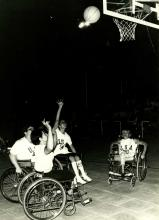 A picture of a woman in a wheelchair shooting a ball during a basketball match