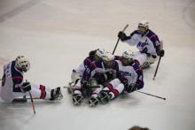 A picture of men sitting in a sledge celebrating their victory in a hockey match.