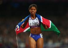 A picture of a woman wearing a Namibian flag celebrating her victory