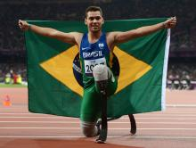 A picture of a man on the track posing with Brazilian flag in his hands