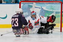A picture of a man in sledge shooting the puck against the goalkeeper in an ice hockey match