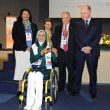 Iranian archer Zahra Nemati seated in a wheelchair holding an award surrounded by people.