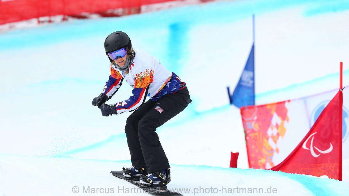 Amy Purdy going over a hill in the snowboard cross course in Rosa Khutor.