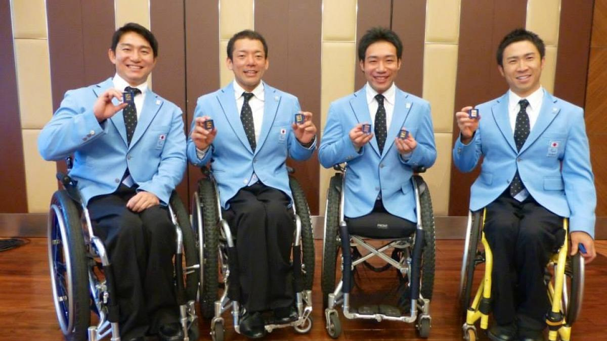 Four men in wheelchairs all wearing blue jackets show pins to the camera, smiling